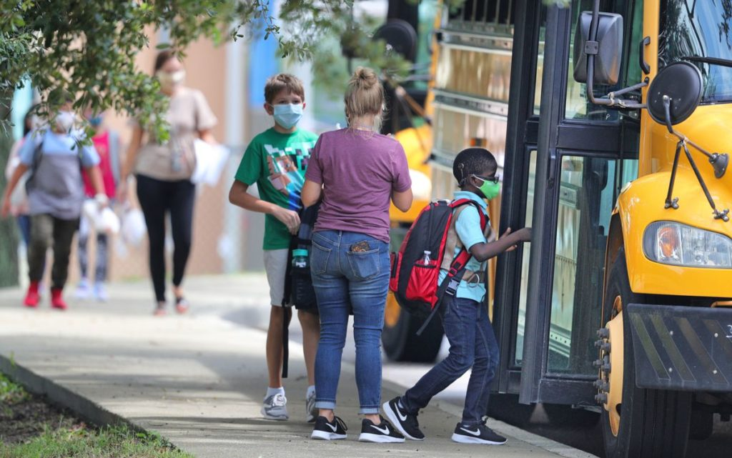 Elementary students board the bus to school in the midst of the COVID-19 pandemic.